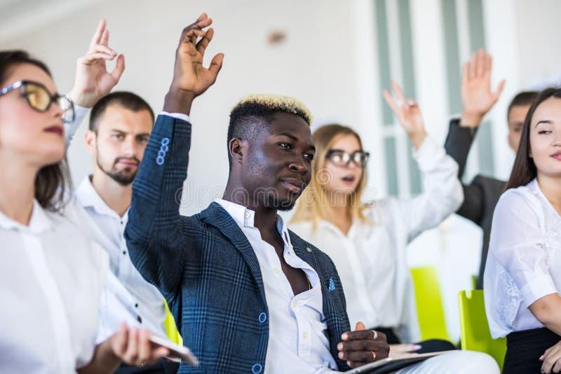 Gruppen av affärsfolk lyfter händer instämmer upp till med högtalaren i mötesrumseminariet äganderätt för home tangent för affärs arkivfoton