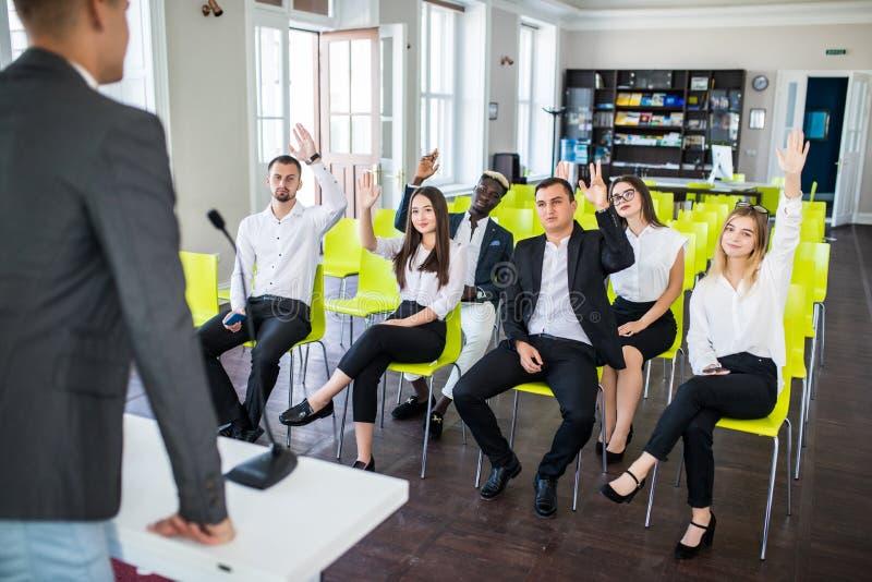 Gruppen av affärsfolk lyfter händer instämmer upp till med högtalaren i mötesrumseminariet Fråga presentatören royaltyfri fotografi