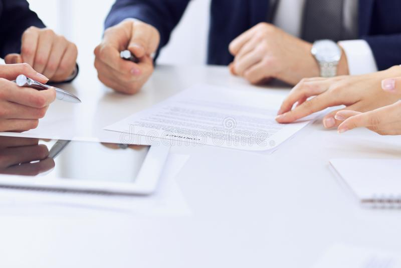 Gruppen av affärsfolk och advokater som diskuterar avtalet, skyler över brister sammanträde på tabellen, närbild lyckad teamwork arkivbilder