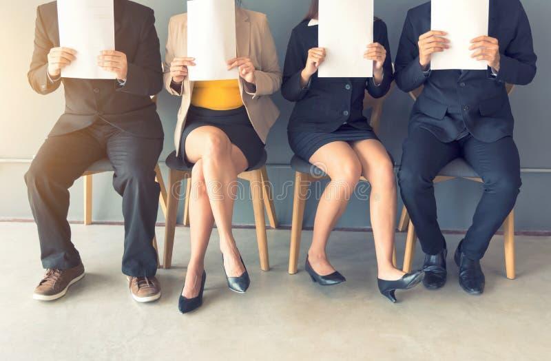 Gruppen av affärsfolk sitter i rad i en kontorslobby arkivbild