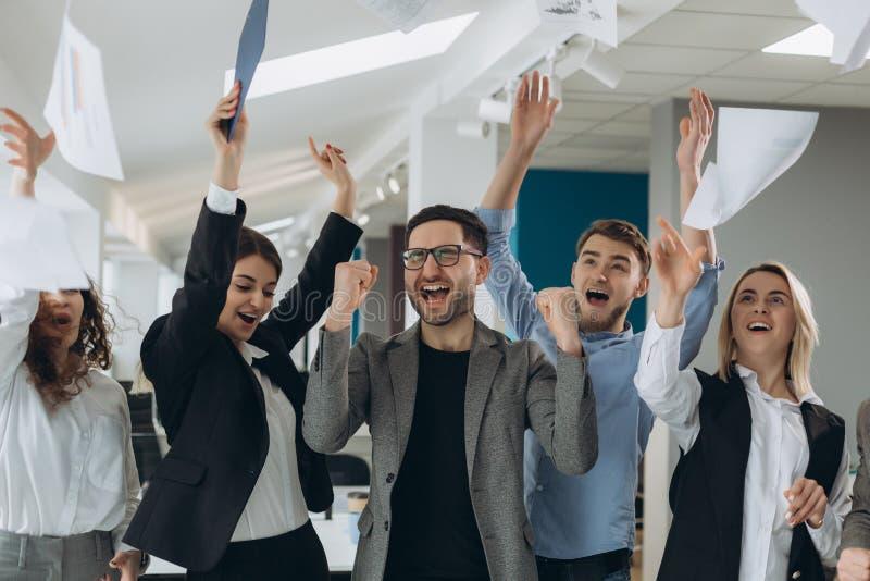 Gruppen av affärsfolk som firar, genom att kasta deras affärslegitimationshandlingar och dokument flyger i luft, makt av samarb royaltyfri fotografi