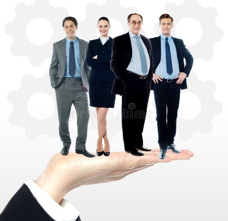 Gruppen av affärsfolk som står på, gömma i handflatan arkivbilder