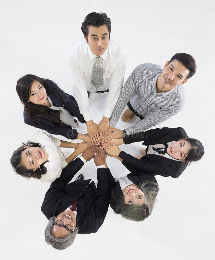 Gruppen av 7 affärspersoner som tillsammans står och, trycker på deras han arkivbilder