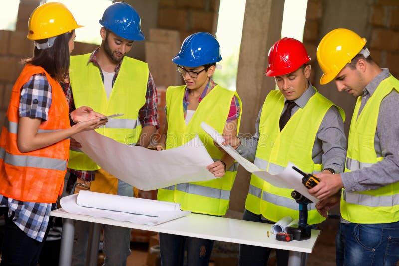 Gruppen av arkitekter och byggnadsarbetare ser det blåa trycket royaltyfri bild