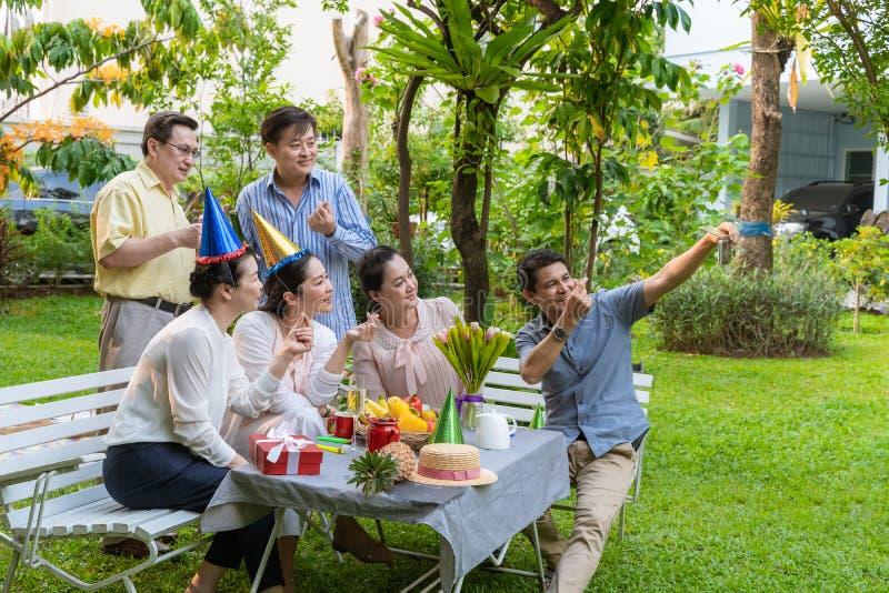 gruppen av asiatiska pensionärer tar bilder av gruppen med deras mobiltelefoner i gyckel på partiet royaltyfri fotografi