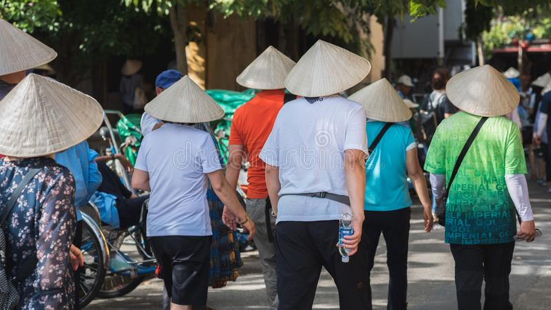 Gruppen av asiatiska turister i vietnamesiska koniska hattar går i gatan i Hoi An royaltyfria foton