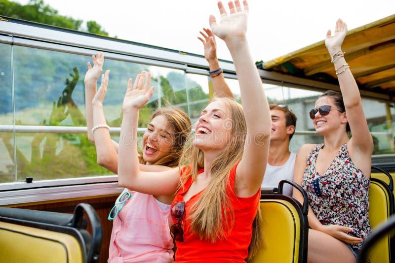 Gruppen av att le vänner som förbi reser, turnerar bussen royaltyfri fotografi