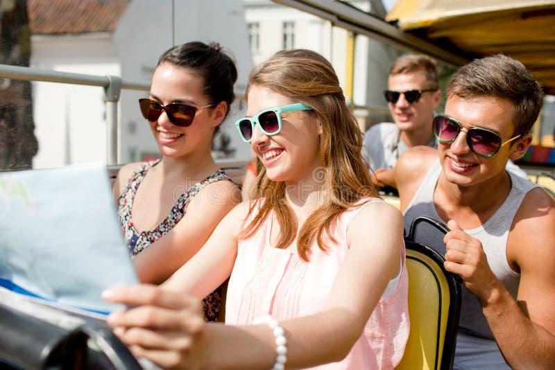 Gruppen av att le vänner som förbi reser, turnerar bussen arkivbild