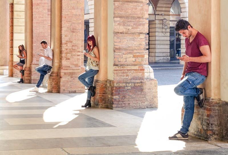Gruppen av barn danar vänner som använder smartphonen i stadsområde royaltyfria foton