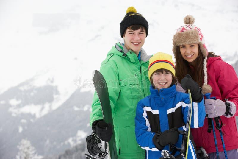 Gruppen av barn skidar på ferie i berg arkivfoton