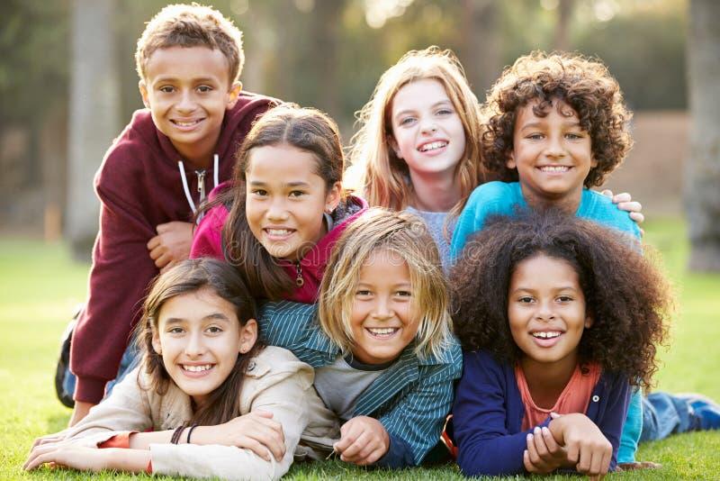 Gruppen av barn som ligger på gräs i, parkerar tillsammans royaltyfri foto