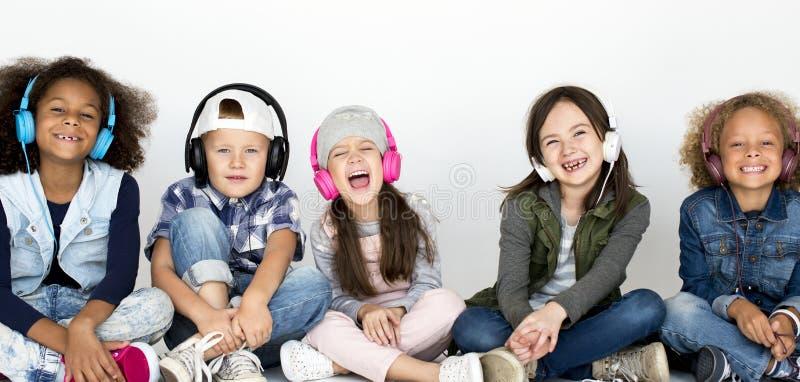 Gruppen av barn tycker om musiken vid hörlurar royaltyfria bilder