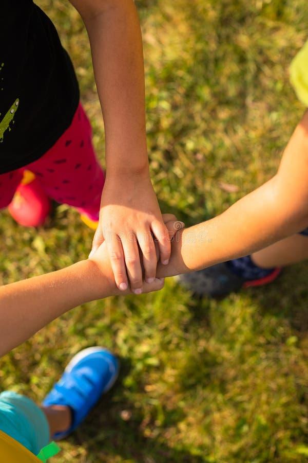 Gruppen av barnhänder sammanfogar tillsammans i kollaborativ lek royaltyfria bilder