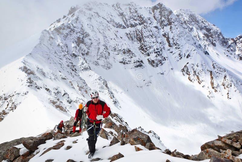 Gruppen av bergsbestigare som stigningen till berget som använder repet på en komplex lutning, komponeras av, vaggar och snöar arkivbild