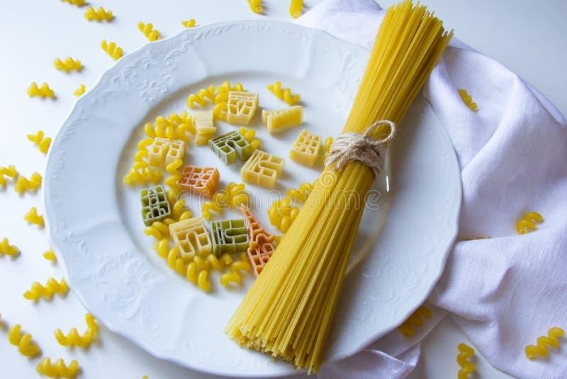 Gruppen av bunden spagetti klibbar på den vita plattan med färgrik fusilli och simbolic pasta på vit bakgrund fotografering för bildbyråer