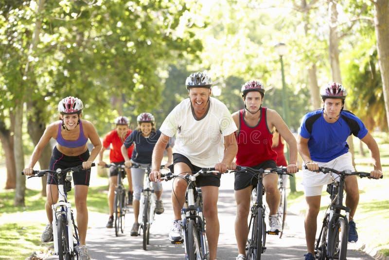 Gruppen av cyklister på cirkuleringsritt parkerar igenom royaltyfria foton