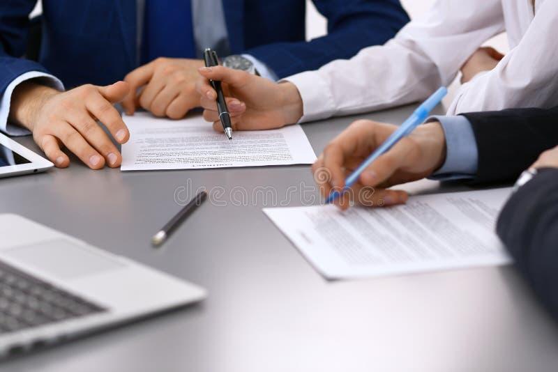 Gruppen av den affärsfolk och advokaten som diskuterar avtalet, skyler över brister sammanträde på tabellen, closeup Affärsmannen royaltyfri foto