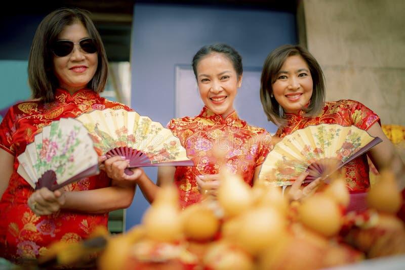 Gruppen av den asiatiska kvinnan som b?r sinnesr?relse f?r lycka f?r framsida f?r kinesisk traditionskl?der toothy le, och handte fotografering för bildbyråer