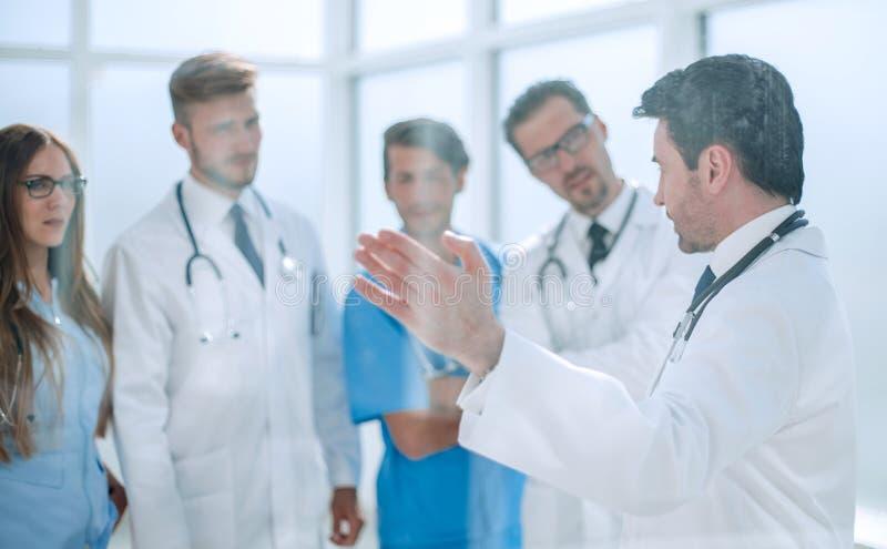 Gruppen av den medicinska personalen diskuterar i korridoren av kliniken royaltyfri fotografi