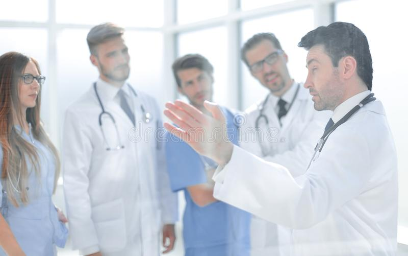 Gruppen av den medicinska personalen diskuterar i korridoren av kliniken arkivbild