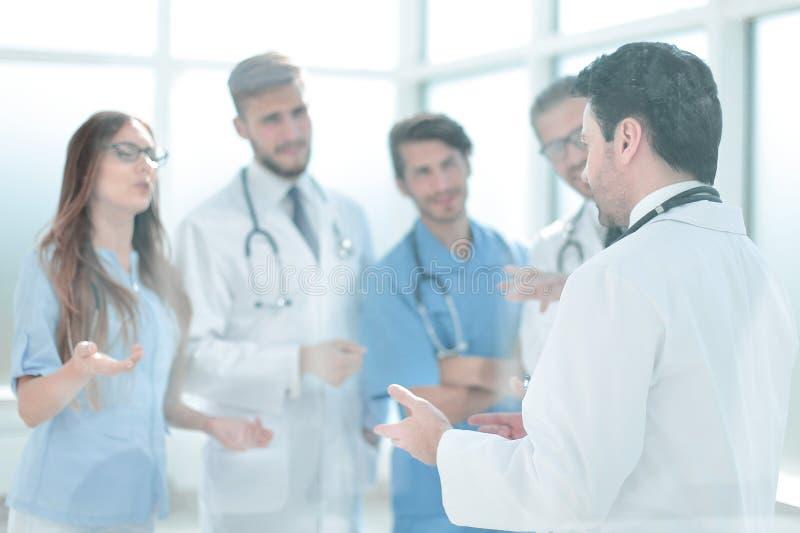 Gruppen av den medicinska personalen diskuterar i korridoren av kliniken royaltyfri bild