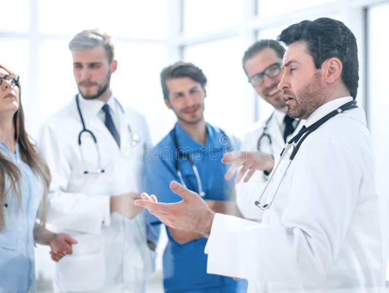Gruppen av den medicinska personalen diskuterar i korridoren av kliniken royaltyfria foton