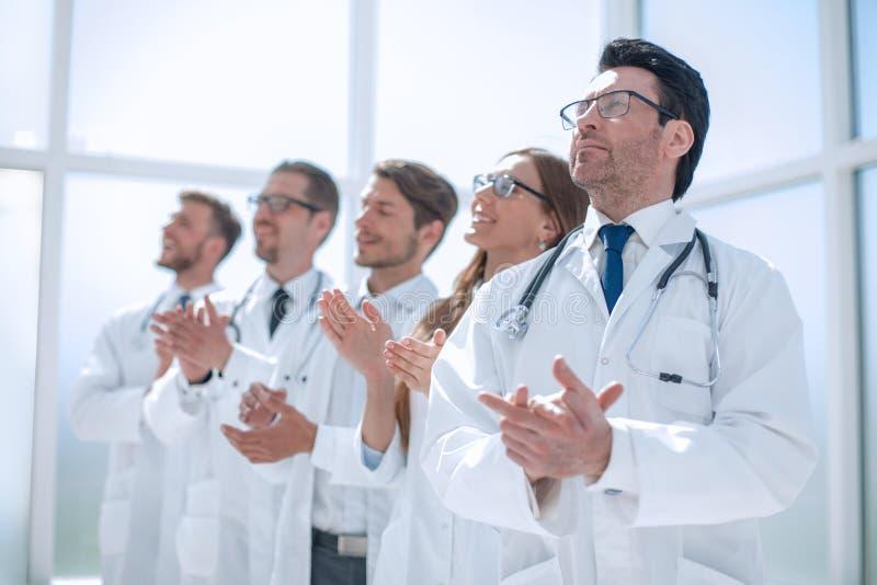 Gruppen av doktorer applåderar och att stå i sjukhuset arkivbilder