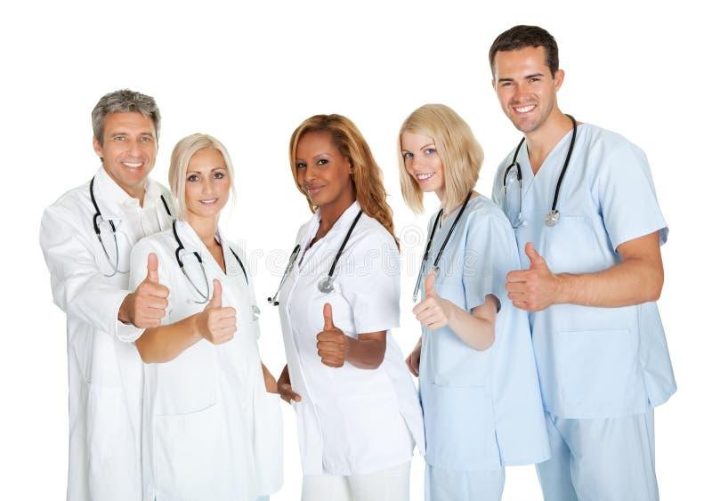 Gruppen av doktorer som ger tummar undertecknar upp, över vit arkivbilder