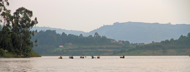 Gruppen av Dugoutkanoter paddlar bort arkivfoton