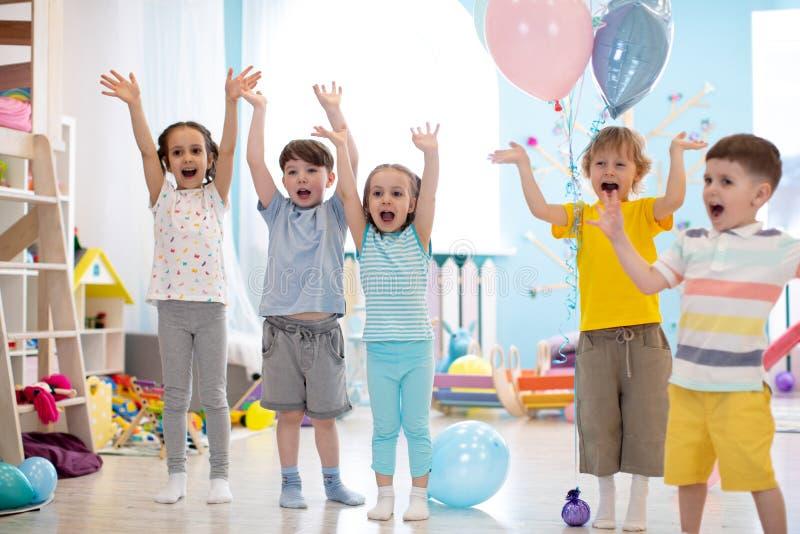 Gruppen av emotionella v?nner med deras h?nder lyftte Ungar har rolig tidsf?rdriv i daycare arkivfoto