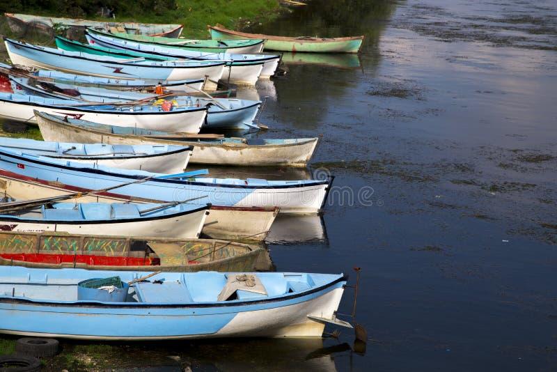 Gruppen av fiskebåtar arrangera i rak linje nära sjön royaltyfri foto