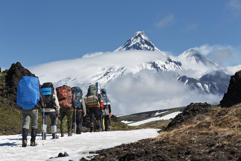 Gruppen av fotvandrare går i berg på bakgrundsvulkan royaltyfri foto