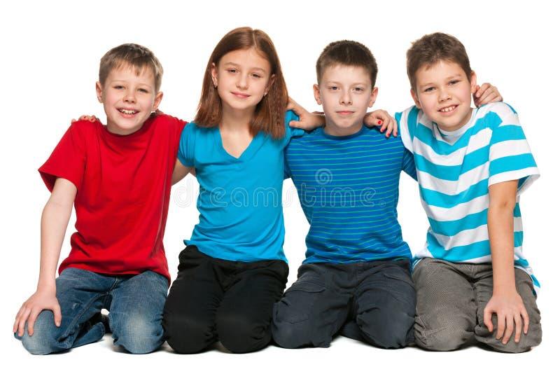 Fyra barn är sammanträde på däcka royaltyfria bilder