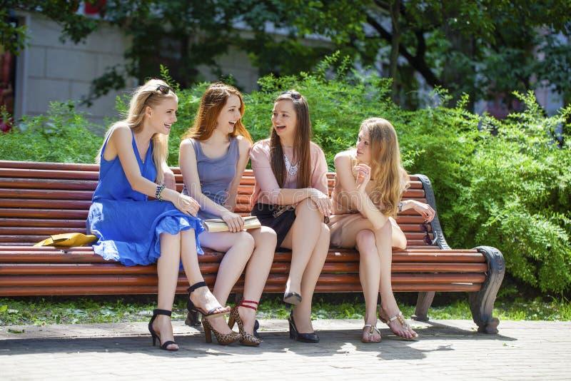Gruppen av fyra unga kvinnor som sitter på bänk i sommar, parkerar royaltyfri bild