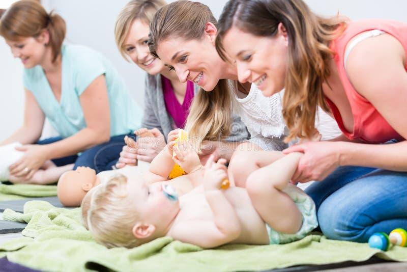 Gruppen av gladlynta kvinnor som lär att ta omsorg av deras, behandla som ett barn royaltyfria bilder