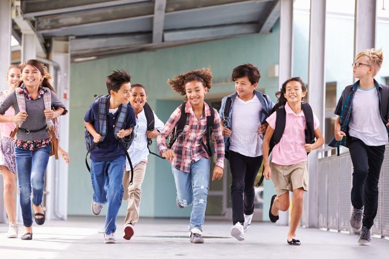 Gruppen av grundskolan lurar spring i en skolakorridor fotografering för bildbyråer