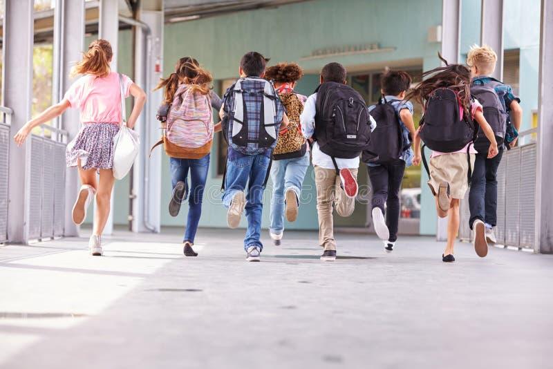 Gruppen av grundskolan lurar spring på skolan, baksidasikt royaltyfria foton