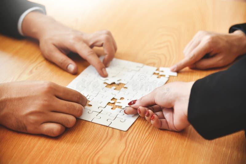 Gruppen av händer för affärsfolk rymmer pusslet arkivfoton
