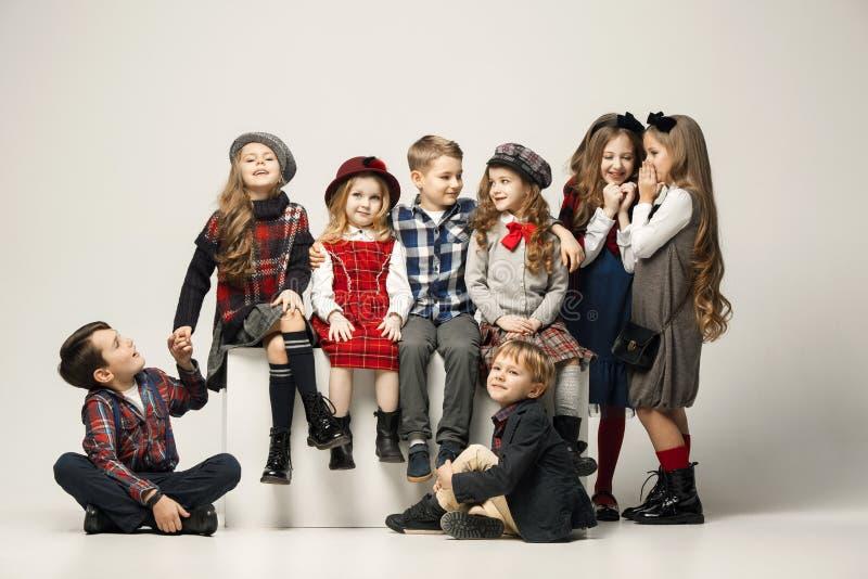 Gruppen av härliga flickor och pojkar på en pastellfärgad bakgrund arkivfoto