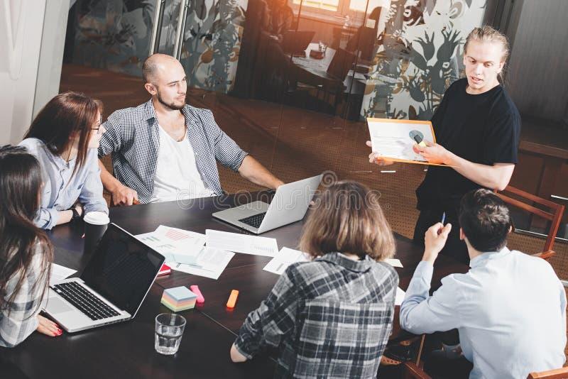 Gruppen av idérika projektchefer analyserar utveckling av starten Affärsfolket arbetar för legitimationshandlingar och bärbar dat arkivfoto