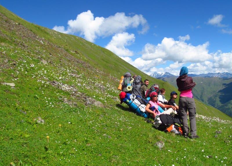Gruppen av klättrare har att vila i den gröna dalen för berget royaltyfri fotografi