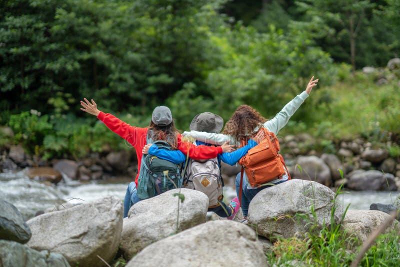 Gruppen av kvinnavänfotvandrare tycker om resande för vägtur och att campa i skogen i helgsommar arkivbilder