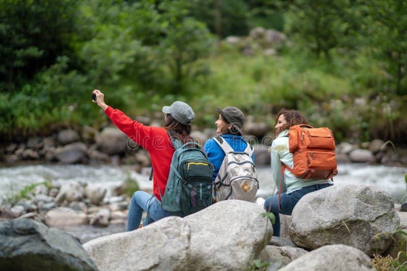 Gruppen av kvinnavänfotvandrare tycker om resande för vägtur och taselfie i skogen i helgsommar royaltyfria foton