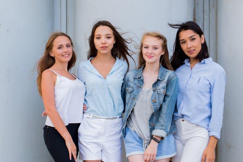 Gruppen av kvinnliga studenter i sommar beklär att posera tillsammans utomhus- och att se kameran arkivbilder