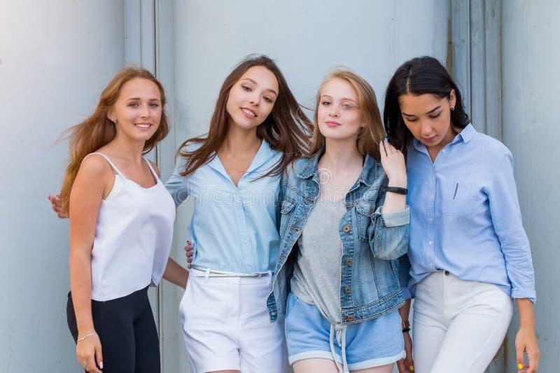 Gruppen av kvinnliga studenter i sommar beklär att posera tillsammans utomhus- och att se kameran Modestående av den unga student arkivfoton
