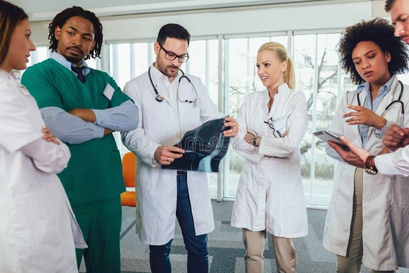 Gruppen av läkare diskuterar röntgenstrålebildläsning royaltyfri bild