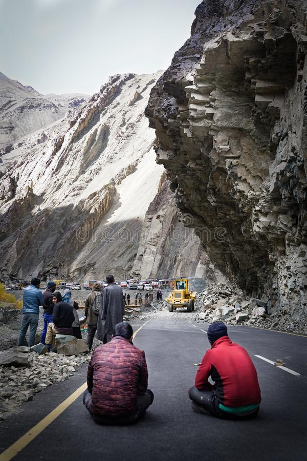 Gruppen av lastbilsförare som väntar, när vägen ska vara klar på grund av jordskred royaltyfri foto