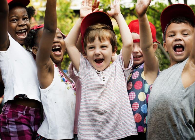 Gruppen av le för lycka för ungeskolavänner handen lyftt lär arkivbild
