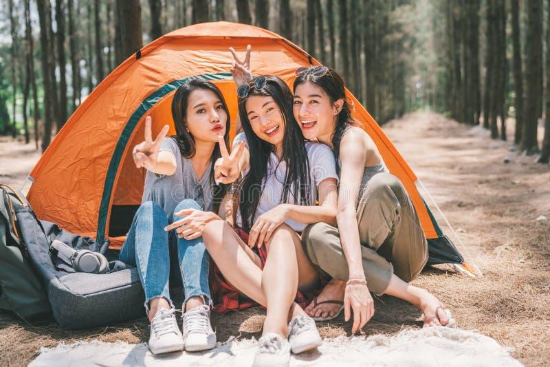 Gruppen av lyckliga asiatiska tonårs- flickor som gör seger, poserar tillsammans och att campa vid tältet Utomhus- aktivitet, aff arkivbild