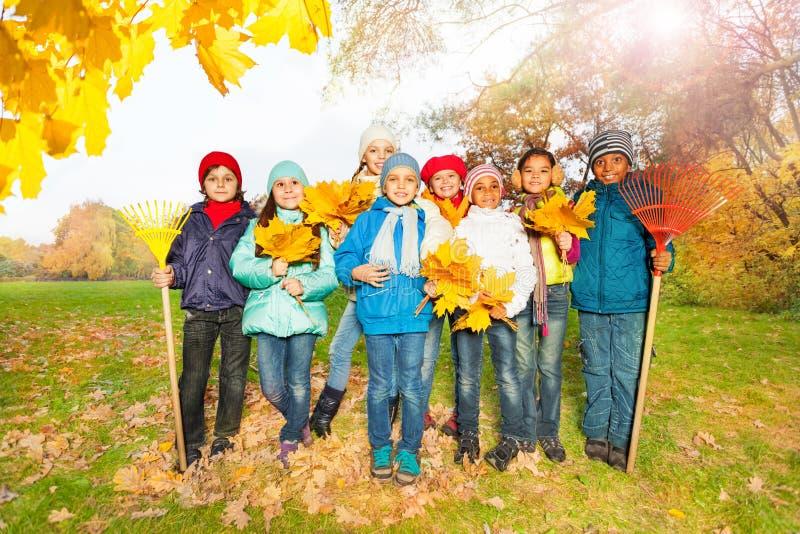 Gruppen av lyckliga barn med krattar och sidor royaltyfri foto